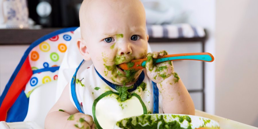 messy baby eating from spoon